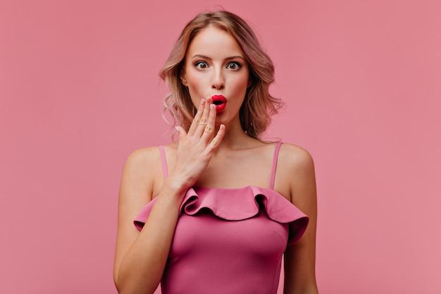 Gelukkig vrolijke vrouw in roze-passende katoenen jurk demonstreert haar verbazing en poseert voor de camera in de buurt van de roze muur