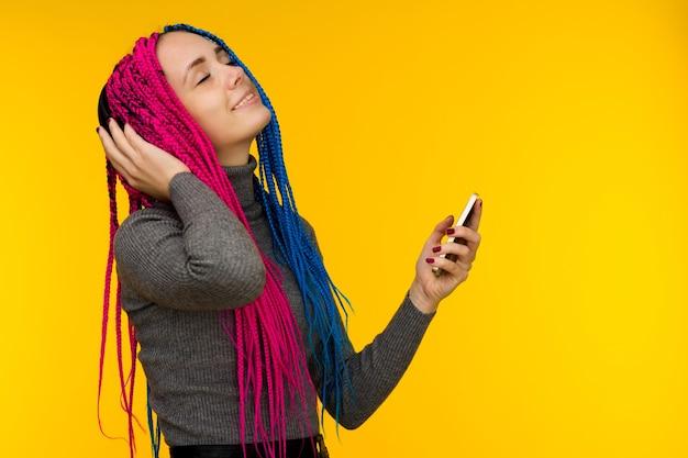 Gelukkig vrolijke vrouw met senegalese vlechten en sproeten draadloze koptelefoon dragen