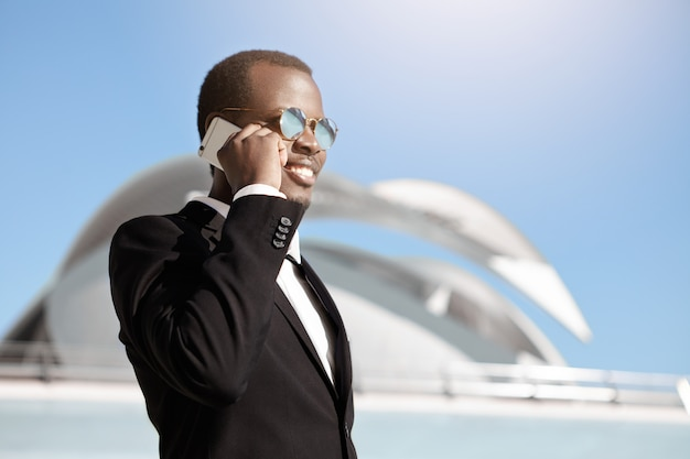 Gelukkig vrolijke zwarte zakenman in formele slijtage en zonnebril praten op smartphone buiten kantoor bouwen vroeg in de ochtend, afspraak maken voor zakelijke bijeenkomst met potentiële partners