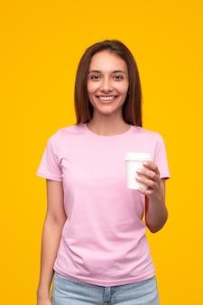 Gelukkig vrouw in roze t-shirt glimlachen en kijken terwijl u geniet van koffie om te gaan