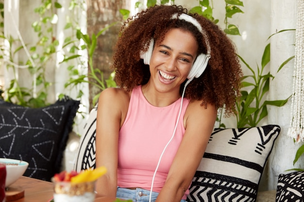 Gelukkig vrouw met donkere gezonde huid, luistert online anekdotes met speciale applicatie en koptelefoon, lacht om grappige grap, zit op comfortabele bank tegen gezellig café-interieur. mensen en vrije tijd