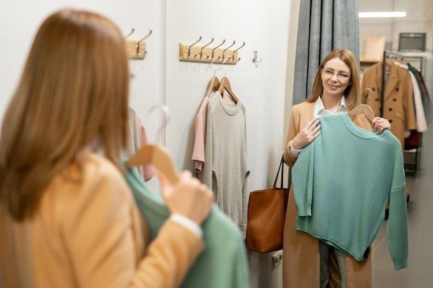 Gelukkig vrouw van middelbare leeftijd in beige jas in de spiegel kijken in de kleedkamer terwijl ze een nieuwe blauwe gebreide trui vasthoudt voordat ze het probeert