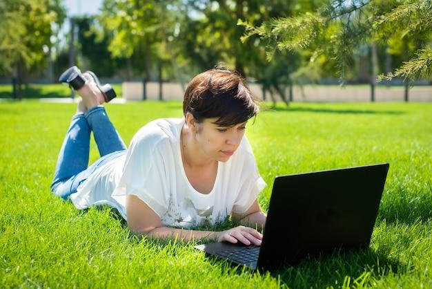 Gelukkig vrouw van middelbare leeftijd liggend op groen gras met behulp van laptopcomputer in het park.
