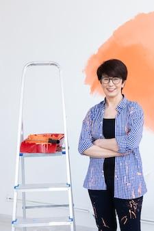 Gelukkig vrouw van middelbare leeftijd schilderen binnenmuur met verfroller in nieuw huis.