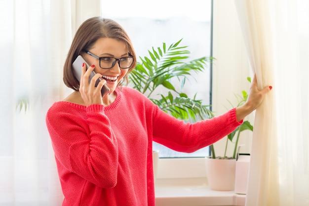 Gelukkig vrouw van middelbare leeftijd vrouwelijke praten op mobiele telefoon