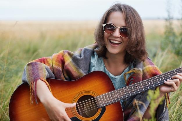 Gelukkig vrouwelijk het leren het spelen gitaar terwijl het zitten in groenland dat pret heeft. mooie vrouw die zonnebril draagt die goed humeur heeft terwijl het spelen van muziekinstrument