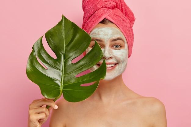 Gelukkig vrouwelijk model heeft een diepe reiniging met gezichtsmasker, bedekt de helft van het gezicht met groen blad, verbetert haar uiterlijk, wil een fantastische huid, ontbloot de poriën, lacht zachtjes