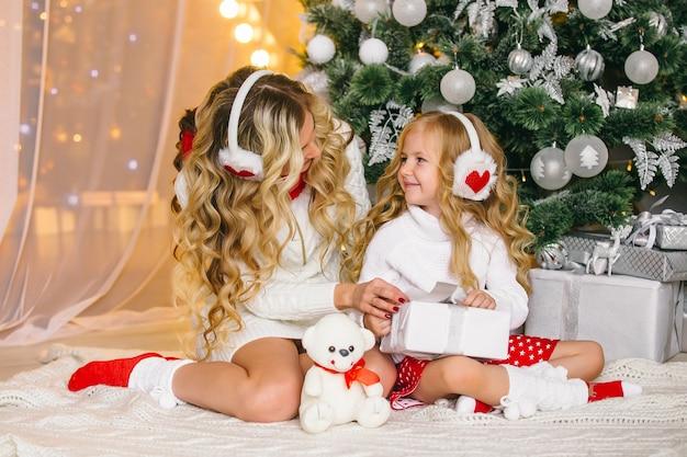 Gelukkig vrouwelijk model met lang blond haar en haar schattige kleine meisje hebben samen plezier om kerstmis te vieren