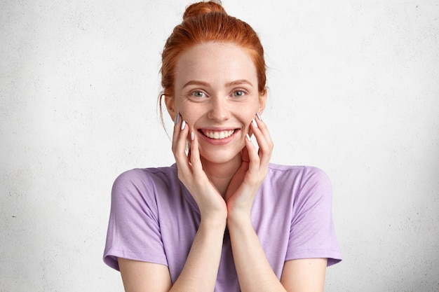 Gelukkig vrouwelijk model met vrolijke uitdrukking, glimlacht breed naar camera, draagt casual paars t-shirt, verheugt zich om weekends door te brengen met naaste mensen in familiekring