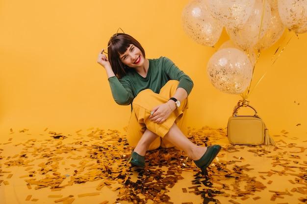 Gelukkig vrouwelijk model zittend op de vloer bedekt met confetti en lachen. betoverende blanke meisje poseren met ballonnen in haar verjaardag.