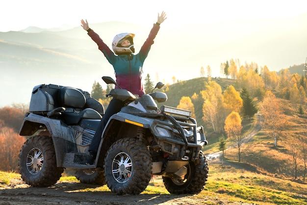 Gelukkig vrouwelijke bestuurder in beschermende helm genieten van offroad rijden op atv quad motor