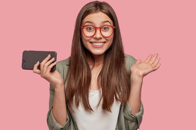 Gelukkig vrouwelijke jongere met aantrekkelijke uitstraling, positieve emoties, handen geklemd, heeft een brede glimlach