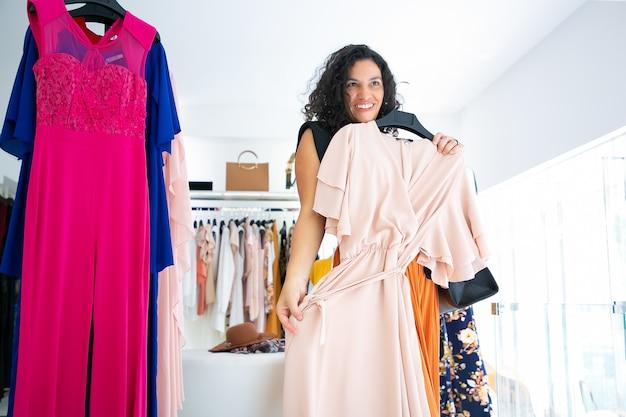 Gelukkig vrouwelijke klant jurk met hanger toe te passen en in spiegel kijken. vrouw die kleren in modewinkel kiest. winkelen of winkelconcept