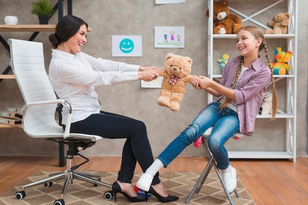 Gelukkig vrouwelijke psycholoog en meisje spelen samen met zachte teddybeer in de kliniek