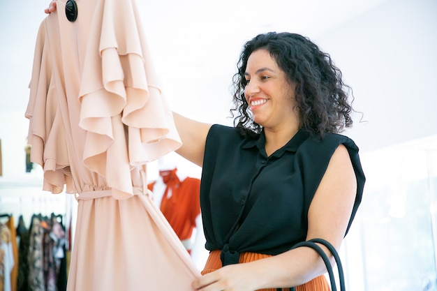 Gelukkig vrouwelijke shopper met hanger met jurk, doek aan te raken en glimlachen. gemiddeld schot. modewinkel of winkelconcept