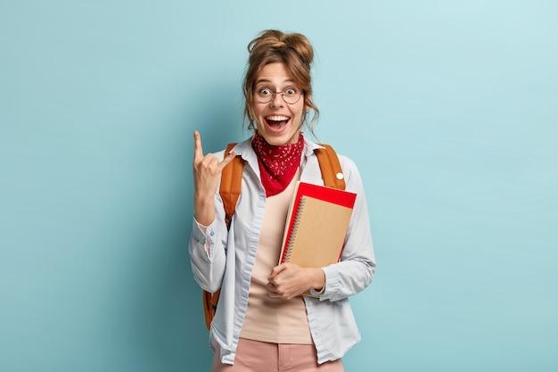 Gelukkig vrouwelijke student met gekamd haar, rock n roll gebaar maakt, heeft blije uitdrukking, verheugt zich op het einde van het studiejaar