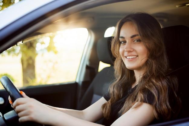 Gelukkig vrouwelijke student rijdende auto net na het ontvangen van rijbewijs