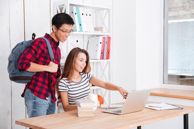 Gelukkig vrouwelijke student wijzend op vertoning van laptop naar haar groepsgenoot. jongen houdt tas vast terwijl hij op laptop kijkt en glimlacht