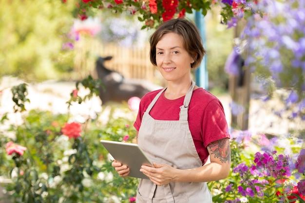 Gelukkig vrouwelijke tuinman met touchpad permanent in kas en online prijslijst voor planten op website werken