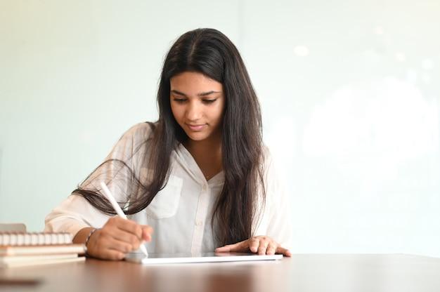 Gelukkig vrouwelijke universiteitsstudent voorbereiden op haar examen op tablet zittend op een houten bureau.