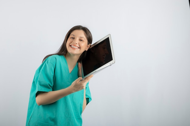 Gelukkig vrouwelijke verpleegster poseren met laptop op wit.