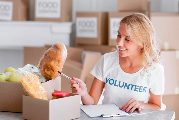 Gelukkig vrouwelijke vrijwilliger voedsel aanbrengend dozen voor donatie
