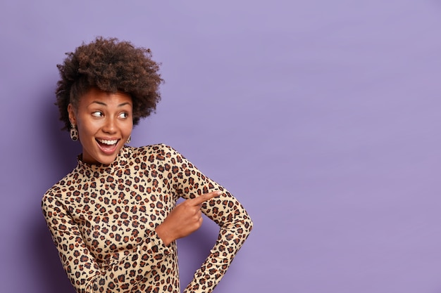 Gelukkig vrouwelijke vrouw met krullend kapsel, wijsvinger naar rechts wijst, bespreekt mooie promo, geeft richting om ruimte te kopiëren, draagt luipaard coltrui