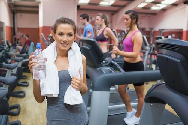 Gelukkig vrouwen drinkwater in gymnastiek