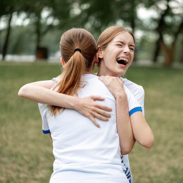 Gelukkig vrouwen knuffelen op voetbalveld
