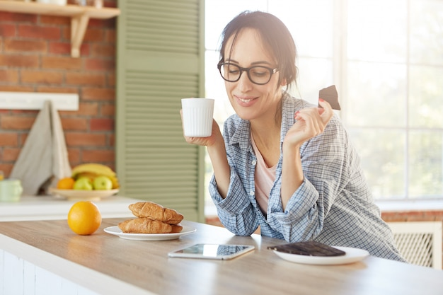 Gelukkig vrouwtje eet zoete chocolade en drinkt thee, kijkt naar grappige film op tablet maakt gebruik van snelle internetverbinding thuis