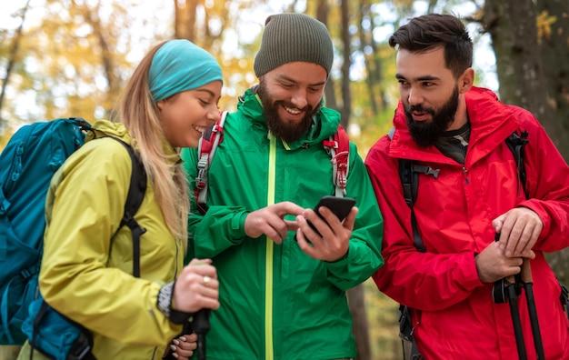 Gelukkig wandelaars met behulp van smartphone in bos