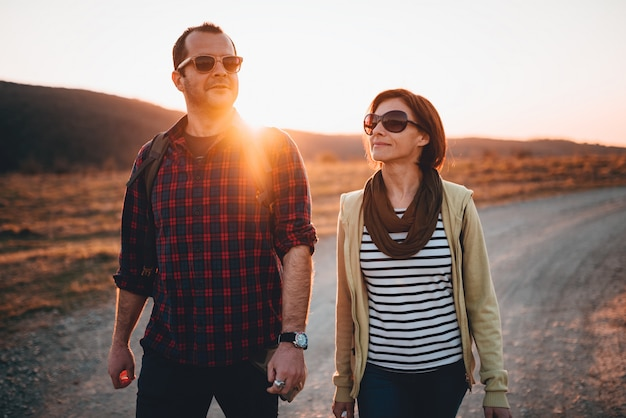 Gelukkig wandelend paar op een landweg tijdens zonsondergang