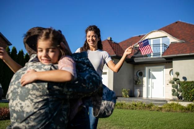 Gelukkig weerzien van soldaat met zijn familie buiten voor hun huis.