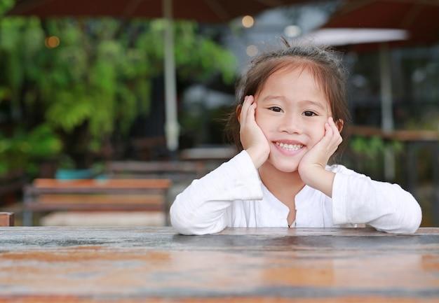 Gelukkig weinig aziatisch jong geitjemeisje die op de houten lijst met het kijken camera liggen