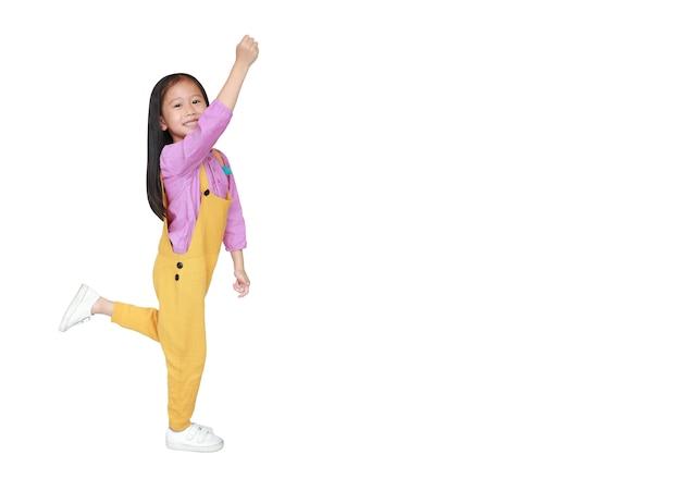 Gelukkig weinig aziatisch kindmeisje in de roze-gele beweging van de grove calico'svrijheid