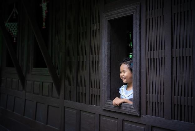 Gelukkig weinig aziatisch meisje dat zich bij het venster bevindt