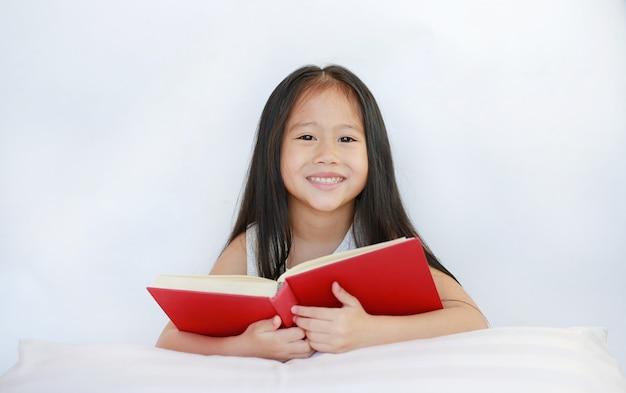 Gelukkig weinig aziatisch meisje die hardcover boek lezen die met hoofdkussen op bed tegen witte achtergrond liggen.