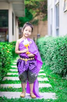Gelukkig weinig aziatisch meisje in thaise periodekleding die zich in het park bevindt