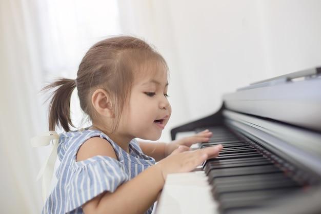 Gelukkig weinig aziatische meisje het spelen piano thuis