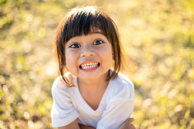 Gelukkig weinig aziatische meisjeskind die voortanden met grote glimlach tonen en lachen: gezond gelukkig grappig lachend gezicht jonge aanbiddelijke mooie vrouwelijke jongen. vrolijk portret van aziatische basisschoolstudent.