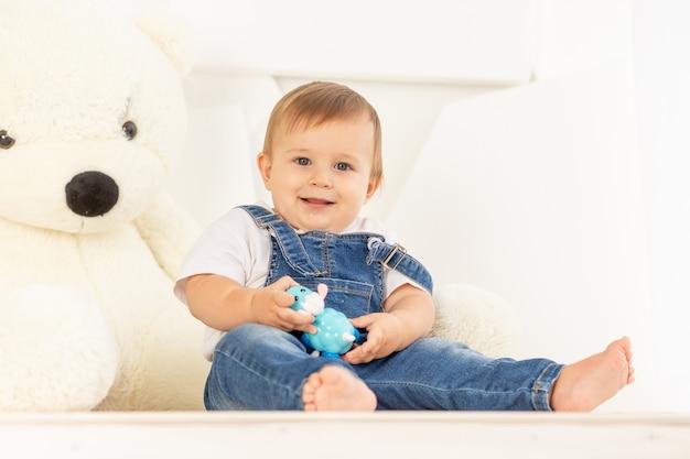 Gelukkig weinig baby zes maanden oud in blauwe spijkerbroek thuis spelen in de buurt van een grote teddybeer