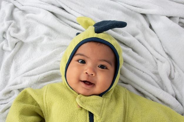 Gelukkig weinig babyjongen die op zachte deken en glimlach ligt