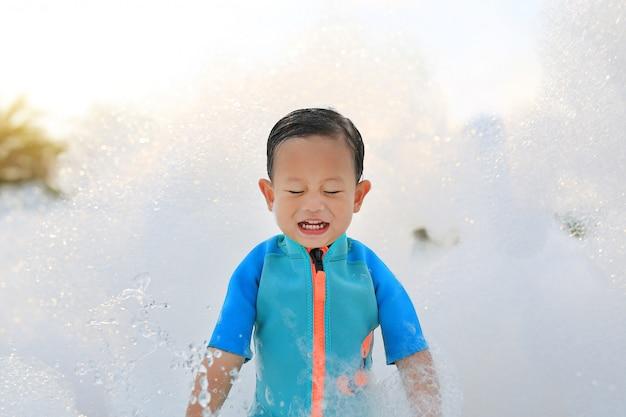 Gelukkig weinig babyjongen in zwempak die pret in schuimpartij hebben bij het zwembad