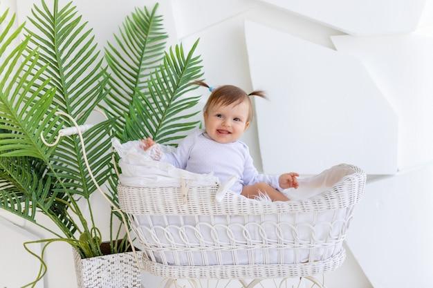Gelukkig weinig babymeisje, zittend in een mooie wandelwagen in een witte romper thuis