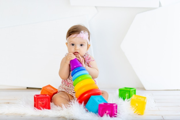 Gelukkig weinig babymeisje, zittend in een witte kamer in een rode jurk met lichte speelgoed