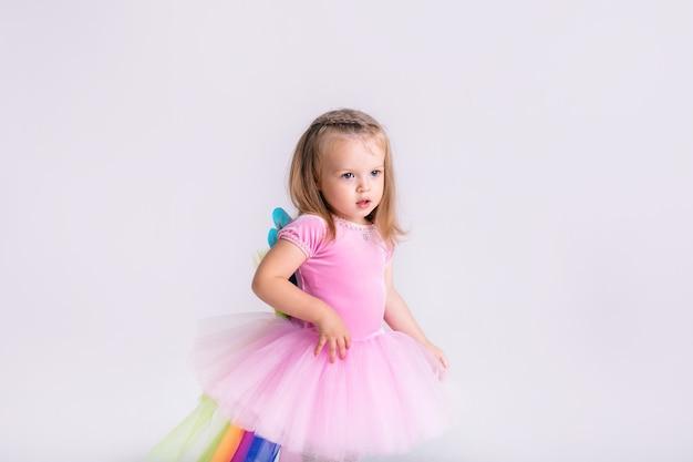 Gelukkig weinig grappig emotioneel kindmeisje in leuk roze de poneykostuum van kerstmis