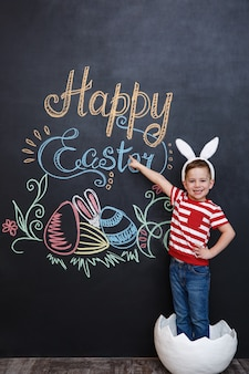 Gelukkig weinig jongen die konijnoren draagt en zich binnen grote gebarsten eierschaal bevindt