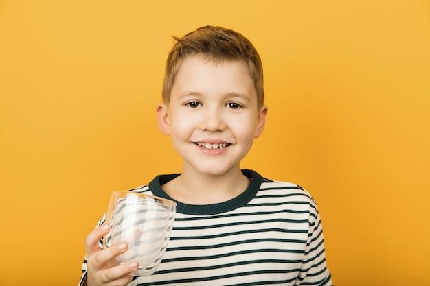 Gelukkig weinig jongen die met melksnor leeg geïsoleerd glas houdt. melkvoordelen, gezond voedselconcept.