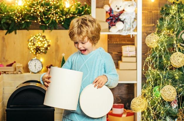 Gelukkig weinig jongenskind met heden of giftdoos binnenshuis. gelukkig schattig kind in kerstmuts met heden