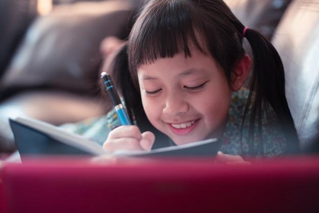 Gelukkig weinig kindmeisje die op bank met het leren door laptop liggen en thuis een boek schrijven, sociale afstand tijdens quarantaine, online onderwijsconcept
